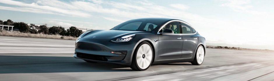 Grijze Tesla Model 3 rijdend